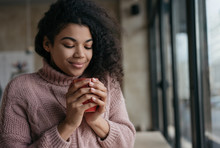 Portrait Of Young Beautiful African American Woman Holding Cup Of Coffee Near Face. Pensive Hipster Girl With Eyes Closed Drinking Tea, Sitting In Cafe