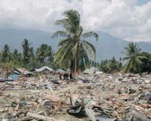 Mid Distance View Of People Standing Amidst Tsunami Destruction Against Cloudy Sky