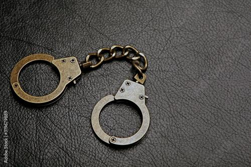 iron handcuffs dark leather background Canvas Print