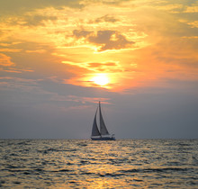 Small Yacht In The Sea At Sunset