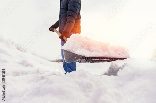 Man working shovel cleaning snow winter street in front of house after big snows Wallpaper Mural