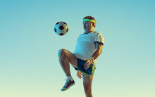 Senior Man Playing Soccer, Football On Gradient Background In Neon Light. Caucasian Male Model In Great Shape Stays Active, Sportive. Concept Of Sport, Activity, Movement, Wellbeing, Healthy Lifestyle