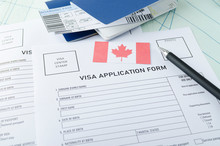 Concept Of Getting Canadian Visa. Blank Visa Application Form, Pen, Passports, Tickets And Canadian Flag On The Map