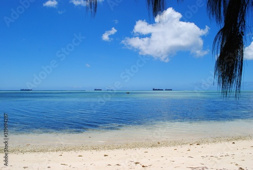 Scenic view of white sandy beach and blue waters in Saipan, Northern Mariana Islands.