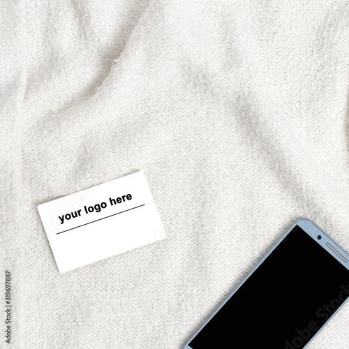 Fotomural Wizytówka i telefon komórkowy leżące na białym kocu.