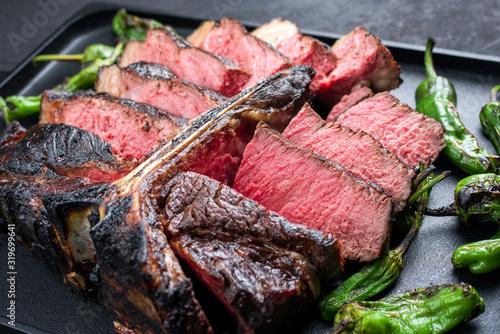 Photo Gegrilltes dry aged Wagyu Porterhouse Rinder Steak aufgeschnitten mit großen Fil