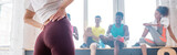 Selective focus of young girl with hands on hips and multiethnic zumba dancers in dance studio, panoramic shot