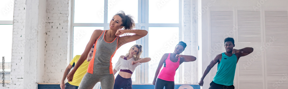 Fototapeta Panoramic shot of african american trainer and young multiethnic dancers practicing zumba in dance studio