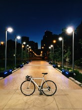 Bicycle Parked On Illuminated Pathway At College Campus