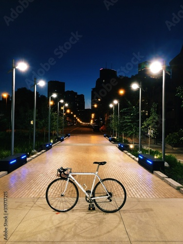 Bicycle Parked On Illuminated Pathway At College Campus - fototapety na wymiar