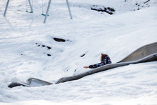 Boy Playing On Slide Over Snow...