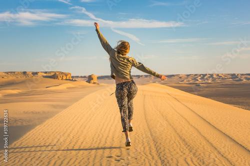 Happy girl jumping in the desert celebrating her freedome