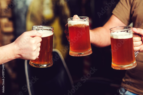 Happy friends drinking beer and clinking glasses at pub Canvas Print