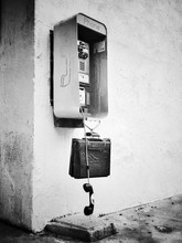 Payphone Against Wall With Receiver Dangling Of The Hook