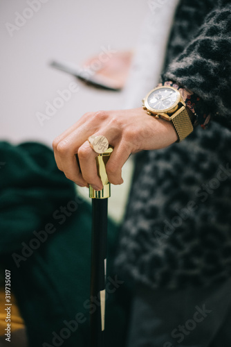 Fotografering GLD RING GOLD CLOCK ON HAND HOLDING GOLDEN STICK PIMP COSTUME