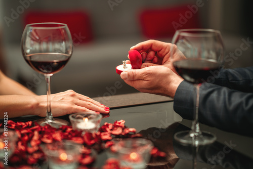 Fototapeta A couple having a romantic dinner and a suprise proposal in a elegance restaurant with beautiful decoration. Romance and Valentines day concept.  obraz