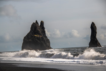 Fototapeta Morze Rocks in the sea on a black sand beach
