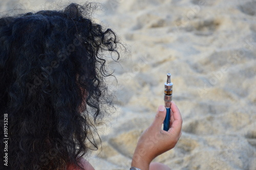 Photo Rear View Of Woman Holding Electronic Cigarette At Beach