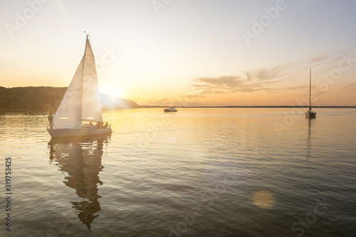 Sailing boats coming back into the harbor during beautiful sunset at the Baltic Fototapeta