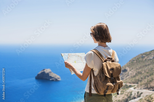 Fotografía Beautiful tourist woman holding map, traveler girl looking for hiking route with sea and mountain at background