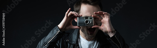 Photo stylish brutal man in biker jacket taking picture on film camera with open mouth