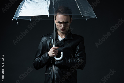 Fényképezés angry stylish brutal man in biker jacket with umbrella isolated on black