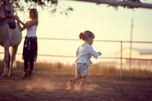 Little Girl Running Around On The Ranch. Fun On Countryside, Sunset Golden Hour. Freedom Nature Concept.