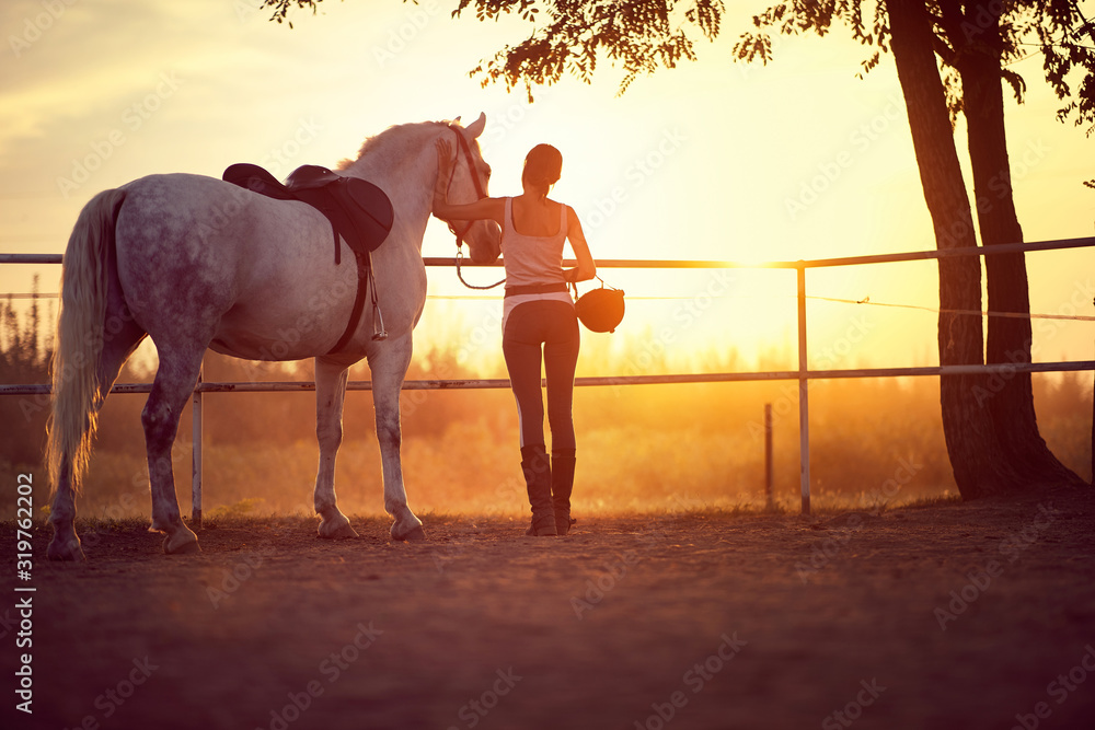 Fototapeta Woman and her horse watching the sunset. Fun on countryside, golden hour. Freedom nature concept.