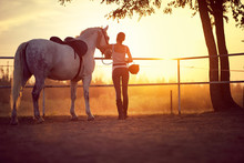 Woman And Her Horse Watching The Sunset. Fun On Countryside, Golden Hour. Freedom Nature Concept.