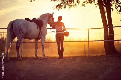 Woman and her horse watching the sunset Canvas Print
