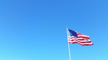 LOW ANGLE VIEW OF AMERICAN FLAG AGAINST CLEAR BLUE SKY
