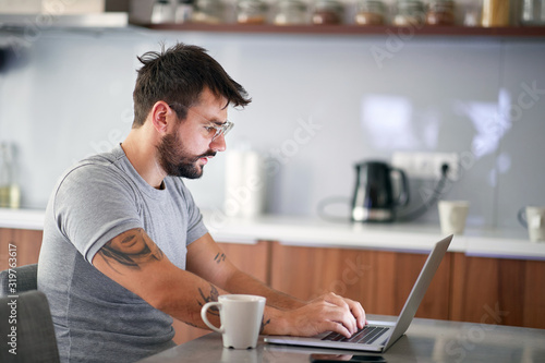 Obraz  man  in the morning checking email on a laptop - fototapety do salonu