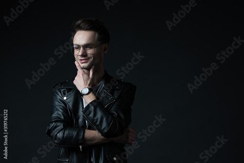 smiling dreamy stylish brutal man in biker jacket isolated on black Fototapet