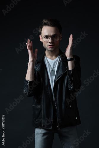 worried stylish brutal man in biker jacket gesturing isolated on black Tablou Canvas
