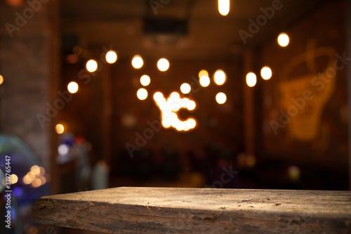 Fototapeta Blurred cafe bar, restaurant, club, blurred light golden bokeh background. With wooden tables in focus. obraz na płótnie