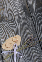 Wedding Rings Lie On Hearts Cut Out Of Paper. Near A Bunch Of Lavender. On Brushed Pine Boards Painted In Black And White.
