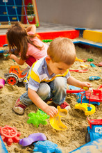 Creative Activities For Kids. Happy Kids Playing In Sandbox Outdoors