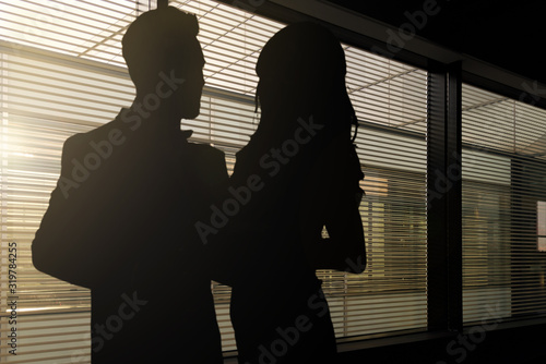 Concept image of romance at work - silhouettes of a woman and a man hugging each Wallpaper Mural