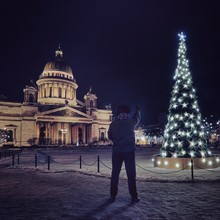 Man Pointing At Christmas Tree Outside St Isaac Cathedral At Night
