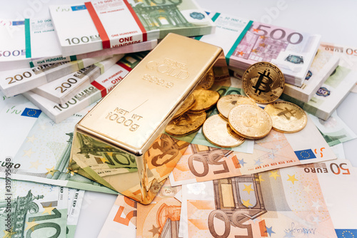 Bitcoin BTC Gold coins with bills of euro banknotes and gold bullion. Bitcoin and gold lie on Euro banknotes