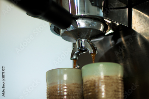 Fototapeta Coffee Maker Pouring Coffee Into Cups