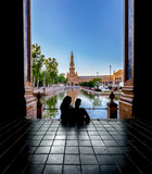 Silhouettes of young couple enjoying the sunset in the famous Spain Square (Plaza de Espana). Seville, Spain.