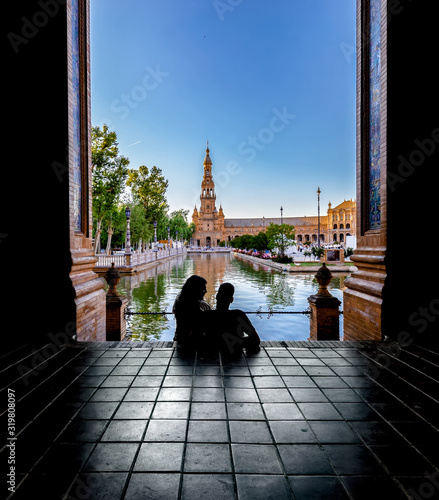 Silhouettes of young couple enjoying the sunset in the famous Spain Square (Plaza de Espana). Seville, Spain. Fototapete