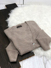 Brown Cardigan Folded On A White Fur Background