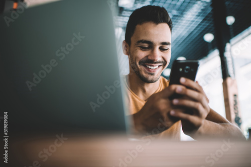 Obraz  Millennial male laughing watching funny video on smartphone spending free time in cafe interior,successful man blogger satisfied with online earning getting income on banking account on cellular. - fototapety do salonu