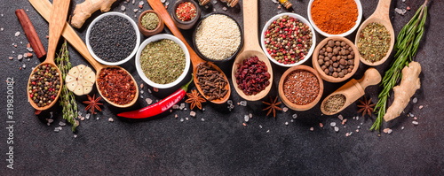 Fotografiet Spices and herbs over black stone background