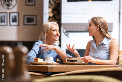 Fotomural Mother and her adult daughter spending time together in cafe