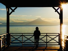 Rear View Of Silhouette Woman Looking At Lake By Mountains In Gazebo During Sunset