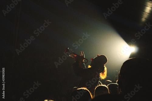 Fotografie, Tablou Spectators Looking At Clown Playing Trumpet In Circus