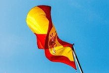 Low Angle View Of Spanish Flag Fluttering Against Blue Sky